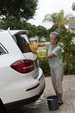 Mujer que lava el parabrisas de un coche blanco del salón Foto de archivo