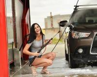 Mujer que lava la sonrisa del coche imagenes de archivo