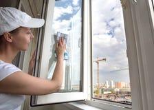 Mujer que lava la ventana Trabajador de sexo femenino de la compañía de la limpieza imagen de archivo libre de regalías