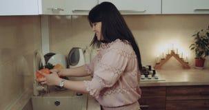 Mujer que lava las legumbres en el fregadero en la cocina Epopeya roja metrajes