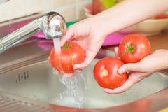 Mujer que lava verduras frescas en cocina Fotografía de archivo libre de regalías