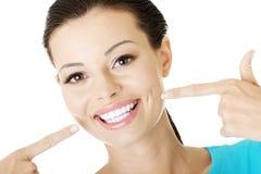 Mujer que le muestra los dientes perfectos. Fotografía de archivo libre de regalías