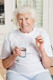 Mujer que le toma la medicina Foto de archivo