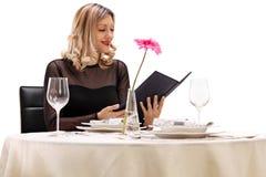 Mujer que lee el menú Fotos de archivo libres de regalías