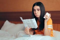 Mujer que lee el prospecto de la medicina antes de tomar píldoras fotos de archivo