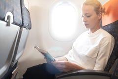 Mujer que lee en vuelo la revista en el aeroplano Lectura femenina del viajero asentada en cabina del passanger Canal brillante d fotos de archivo