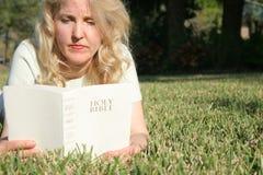 Mujer que lee la biblia santa en GR Fotos de archivo
