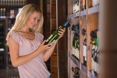 Mujer que lee la etiqueta detrás de una botella de vino Imagen de archivo libre de regalías