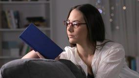 Mujer que lee las lentes que llevan de un libro metrajes