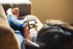 Mujer que lee su teléfono móvil, blog que viaja en la pantalla Imagenes de archivo