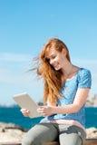 Mujer que lee un eBook en el mar Fotos de archivo