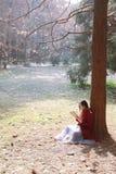 Mujer que lee un ebook o una tableta en un parque urbano, Fotografía de archivo libre de regalías