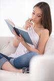 Mujer que lee un libro. Imagen de archivo libre de regalías