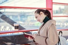 Mujer que lee un libro cerca de los estantes con los libros libres, biblioteca social en la calle Fotografía de archivo