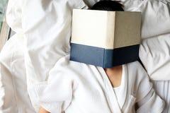 Mujer que lee un libro con la cara cubierta por el libro Fotos de archivo
