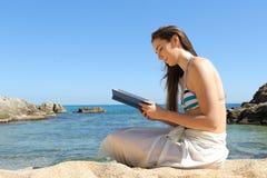 Mujer que lee un libro el vacaciones de verano en la playa imagenes de archivo