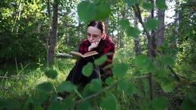Mujer que lee un libro en un bosque verde del verano metrajes