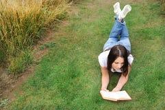 Mujer que lee un libro en césped Imágenes de archivo libres de regalías