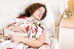 Mujer que lee un libro en cama Fotos de archivo