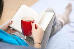 Mujer que lee un libro en cama Foto de archivo
