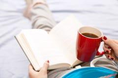 Mujer que lee un libro en cama Fotografía de archivo libre de regalías