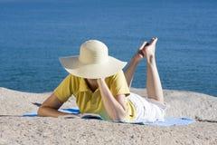 Mujer que lee un libro en el mar Imagen de archivo libre de regalías