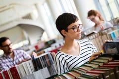 Mujer que lee un libro en la biblioteca Foto de archivo