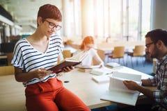 Mujer que lee un libro en la biblioteca Fotografía de archivo libre de regalías