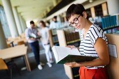 Mujer que lee un libro en la biblioteca Imagen de archivo