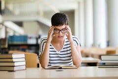 Mujer que lee un libro en la biblioteca Fotos de archivo libres de regalías