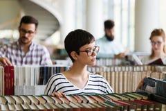 Mujer que lee un libro en la biblioteca Imagenes de archivo