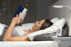 Mujer que lee un libro en la noche en la cama Foto de archivo
