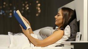 Mujer que lee un libro en la noche en la cama metrajes
