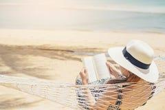 Mujer que lee un libro en la playa de la hamaca en vacaciones de verano del tiempo libre fotos de archivo libres de regalías
