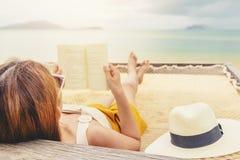 Mujer que lee un libro en la playa de la hamaca en vacaciones de verano del tiempo libre foto de archivo