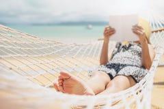 Mujer que lee un libro en la playa de la hamaca en vacaciones de verano del tiempo libre fotografía de archivo