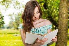 Mujer que lee un libro en parque de la primavera Imagen de archivo