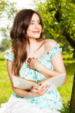Mujer que lee un libro en parque de la primavera Imágenes de archivo libres de regalías