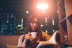 Mujer que lee un libro en un café Imagenes de archivo