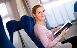 Mujer que lee un libro mientras que en un tren imagen de archivo libre de regalías