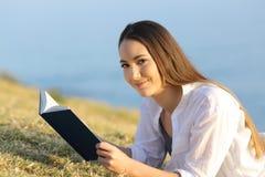 Mujer que lee un libro que mira la cámara en la hierba Fotografía de archivo