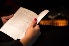 Mujer que lee un libro por la chimenea Foto de archivo libre de regalías