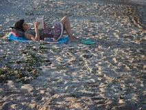 Mujer que lee un libro que miente en la arena en la playa Fotos de archivo libres de regalías