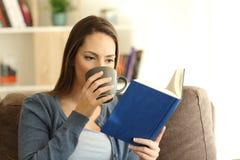 Mujer que lee un libro y que bebe el café Fotos de archivo