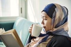 Mujer que lee un libro y un café de la bebida Fotos de archivo libres de regalías