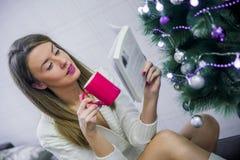 Mujer que lee un libro y que bebe el café en la Navidad en casa en la sala de estar El libro de lectura de la mujer en la Navidad Imágenes de archivo libres de regalías
