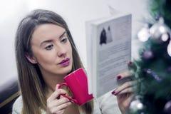 Mujer que lee un libro y que bebe el café en la Navidad en casa en la sala de estar El libro de lectura de la mujer en la Navidad Imagen de archivo libre de regalías