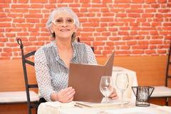Mujer que lee un menú del restaurante cuidadosamente Fotos de archivo libres de regalías