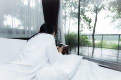 Mujer que lee un mensaje de texto en su dormitorio brillante Fotos de archivo