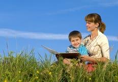 Mujer que lee a un muchacho de los jóvenes del libro imágenes de archivo libres de regalías